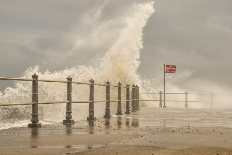Ninguna muestra de baño como ondas de la tormenta del alto mar se rompe sobre el brazo del puerto imagenes de archivo