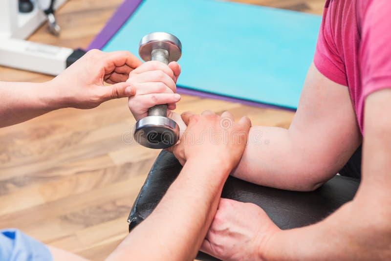 Ninguna mujer mayor de la cara que hace el active, trabajando con pesa de gimnasia dirigido por el terapeuta físico en el centro  fotografía de archivo libre de regalías