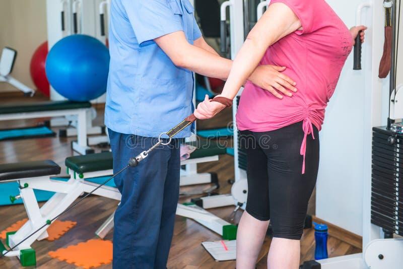 Ninguna mujer mayor de la cara que hace los ejercicios activos, especiales dirigidos por el terapeuta físico en el centro de reha fotografía de archivo libre de regalías