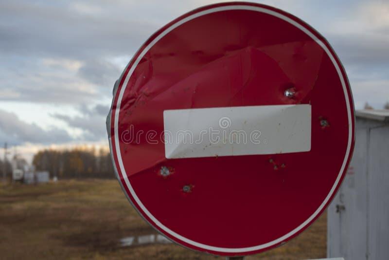Ninguna señal de tráfico con los agujeros de bala, ejercicios de tiro de la entrada imagen de archivo libre de regalías
