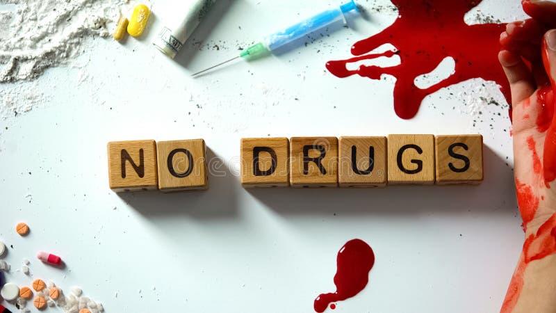 Ningunas drogas expresan en los cubos de madera, la mano que sangra y el narc?tico en la tabla, concepto foto de archivo libre de regalías