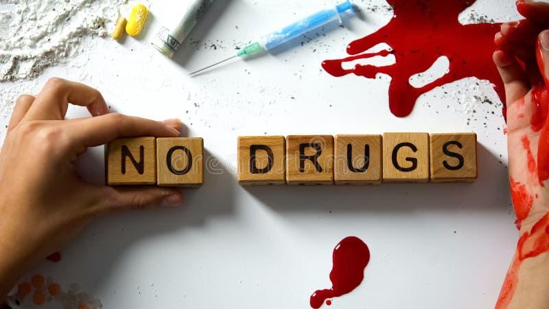 Ningunas palabras de las drogas en los cubos de madera, la mano que sangra y el narc?tico en la tabla, concepto imagenes de archivo