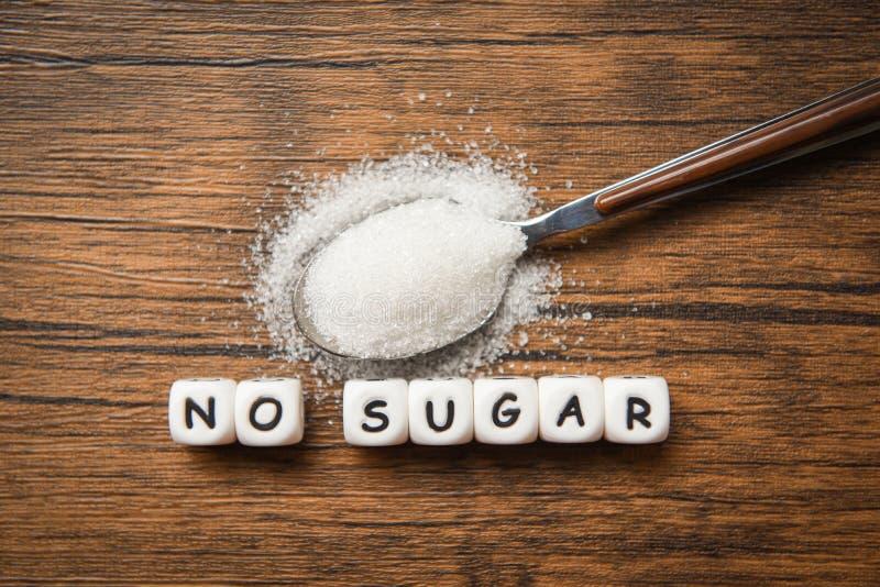 Ningunos bloques de texto del azúcar con el azúcar blanco en fondo de madera de la cuchara - sugiriendo la dieta y comer menos az imagen de archivo