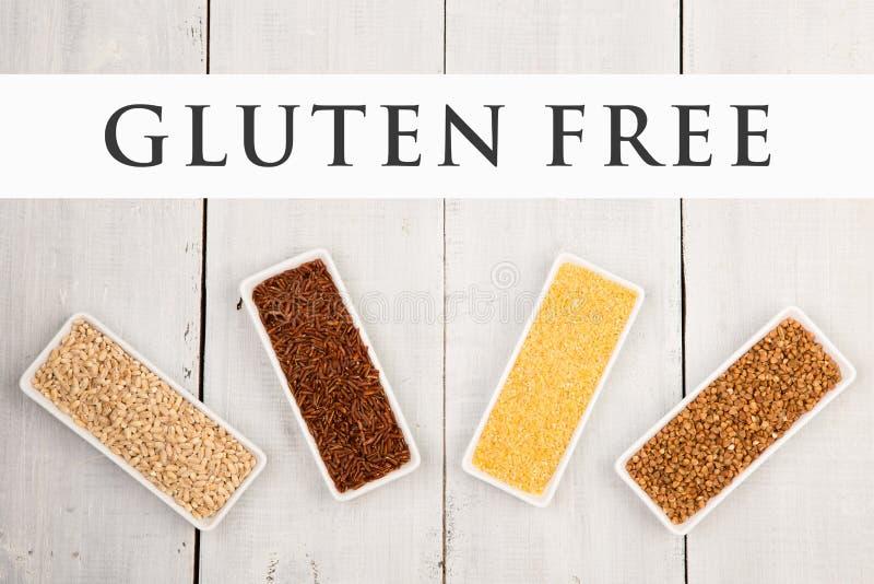 Ningunos cereales del gluten en los cuencos - arenas de maíz, alforfón marrón, arroz rojo, cebada de perla con el gluten del text imagen de archivo