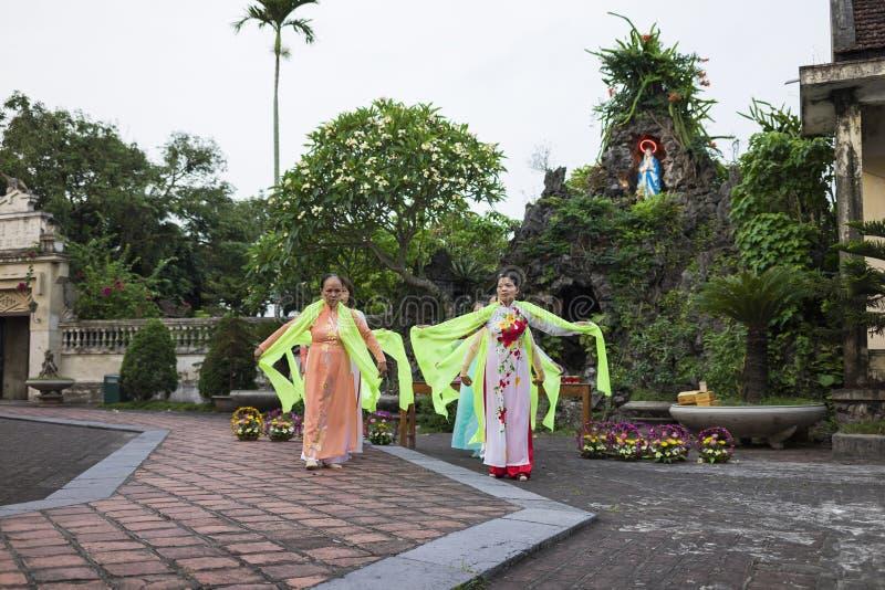 Ninh Binh, Βιετνάμ - 16 Μαΐου 2015: Οι βιετναμέζικες χριστιανικές γυναίκες εκτελούν έναν παλαιό παραδοσιακό χορό στο λουλούδι που στοκ εικόνα με δικαίωμα ελεύθερης χρήσης