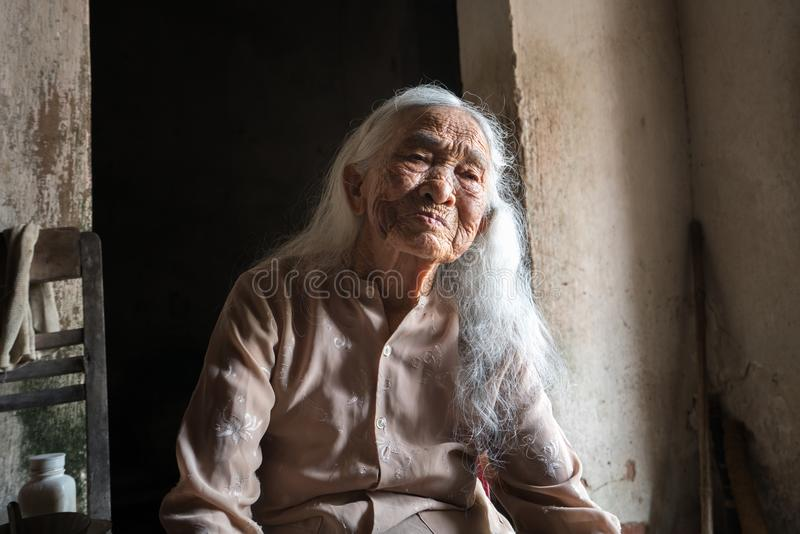 Ninh Binh, Vietnam - Apr 10, 2017: Portrait of an elderly woman with white hair living alone in the very old and poor house. stock photography