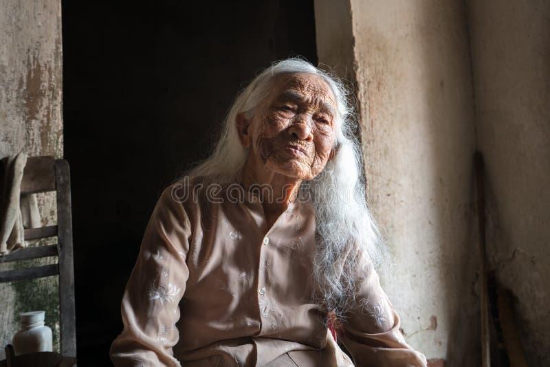 Ninh Binh, Vietnam - 10. April 2017: Porträt einer älteren Frau mit dem weißen Haar allein lebend im sehr alten und im Armenhaus stockfotografie
