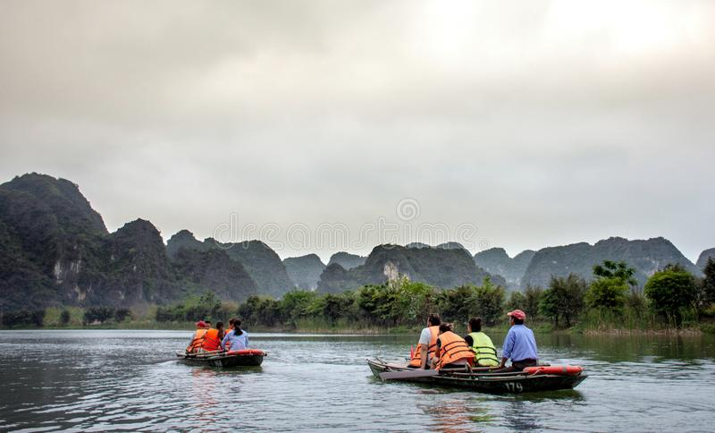 NINH BINH, Vietnam - April 22, 2018: Tourists traveling in small boat along the Ngo Dong River at Trang An royalty free stock image