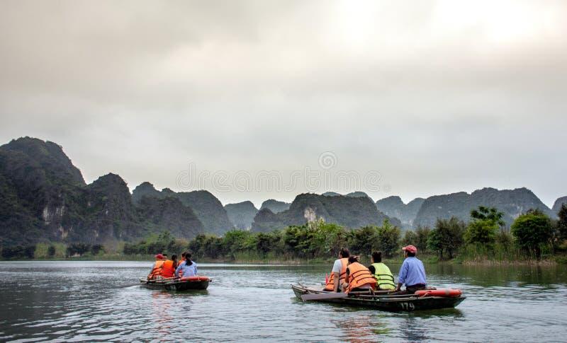 NINH BINH, Vietnam - April 22, 2018: Turister resa i litet fartyg längs Ngo Dong River på Trang royaltyfri bild