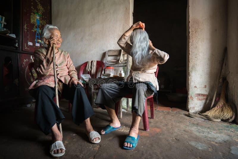 Ninh Binh, Vietnam - 10 April, 2017: Twee bejaarden met wit haar in het zeer oude en slechte huis De oudere zuster bezoekt y stock foto
