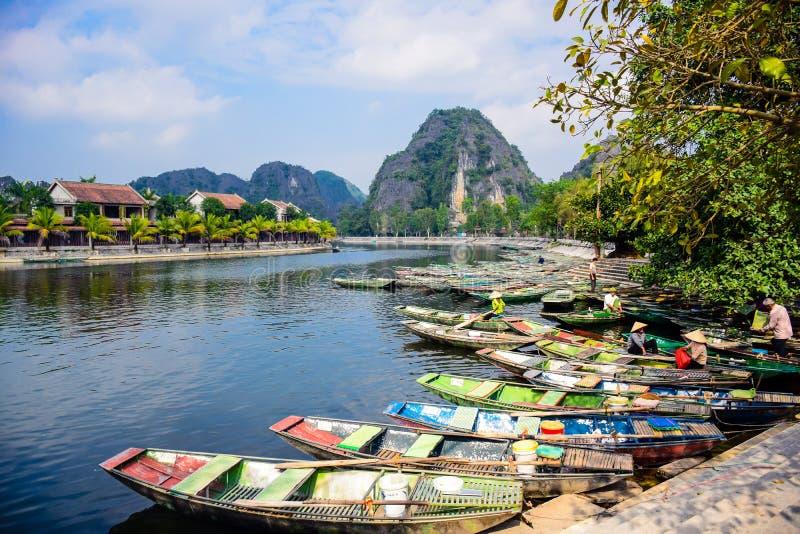 NINH BINH, VIETNAM: Veel die boten op toeristen voor holreizen in Ngo Dong River in Tam Coc, Ninh Binh P wachten stock foto