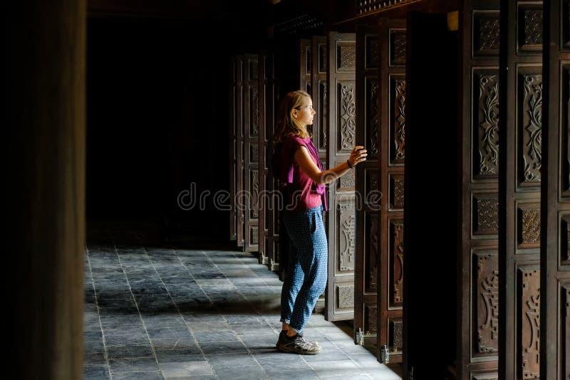 Ninh Binh/Vietnam, 08/11/2017: Vrouw die zich in een traditionele houten deuropening van een Boeddhistische tempel in Trang grott stock afbeeldingen