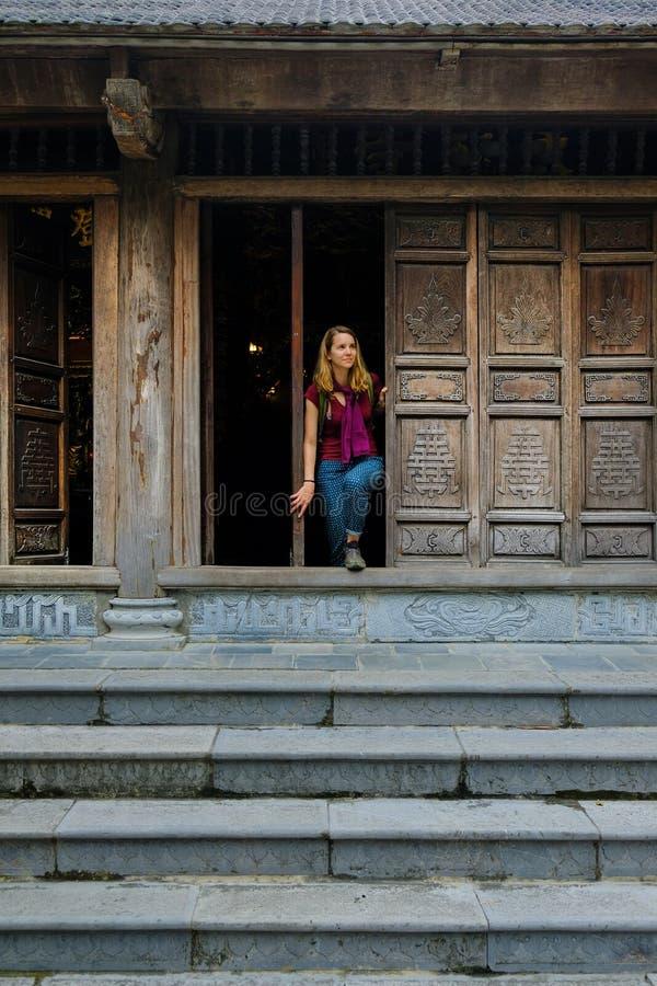 Ninh Binh/Vietnam, 08/11/2017: Vrouw die zich in een traditionele houten deuropening van een Boeddhistische tempel in Trang grott royalty-vrije stock afbeeldingen