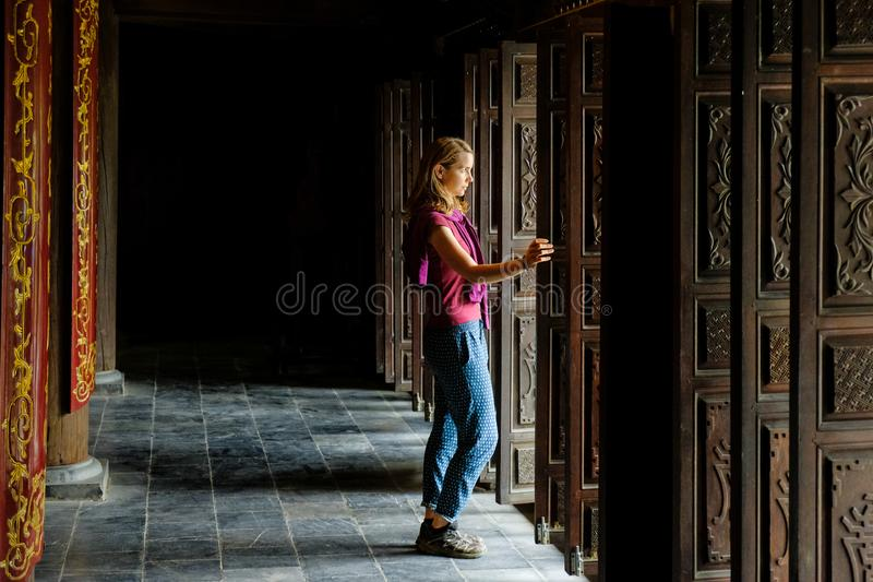 Ninh Binh / Vietnam, 08/11/2017: Woman standing in a traditional wooden doorway of a Buddhist temple in the Trang An grottoes stock images