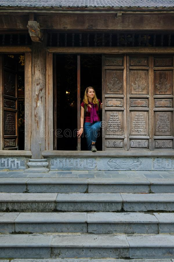 Ninh Binh / Vietnam, 08/11/2017: Woman standing in a traditional wooden doorway of a Buddhist temple in the Trang An grottoes royalty free stock images