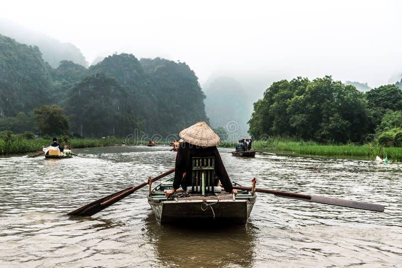 NINHBINH, VIETNAM - MARS 17, 2019: Turister som reser i småbåt i Ngo Dong River, Tamcoc-ekoturism i Ninh arkivbild