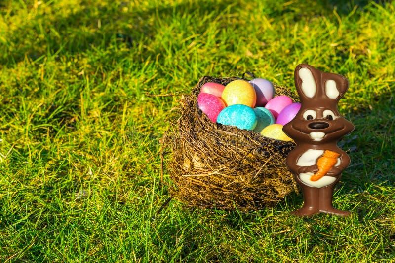 Ninho dos pássaros enchido com os ovos pintados coloridos e um coelhinho da Páscoa do chocolate que está na grama, fundo da Pásco foto de stock