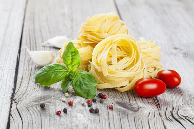 Ninho italiano do fettuccine da massa com alho, manjericão dos tomates foto de stock