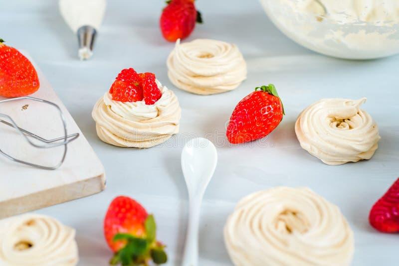 Ninhos do bolo do pavlova da morango, decoração da merengue em uma tabela culinária foto de stock