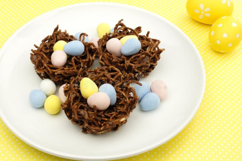 Ninhos do chocolate da primavera no fundo amarelo imagem de stock