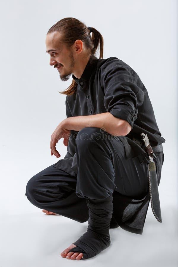 Ninja сидело вниз на одном конце-вверх колена на серой предпосылке стоковые фотографии rf