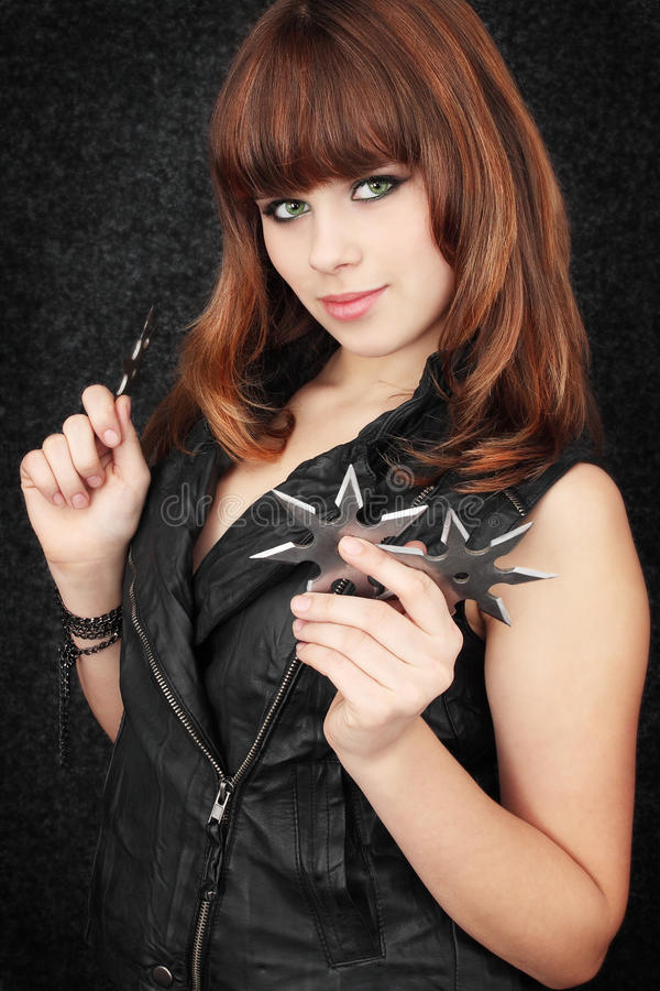 Ninja. Beautiful girl holds in the hands of shuriken royalty free stock photo