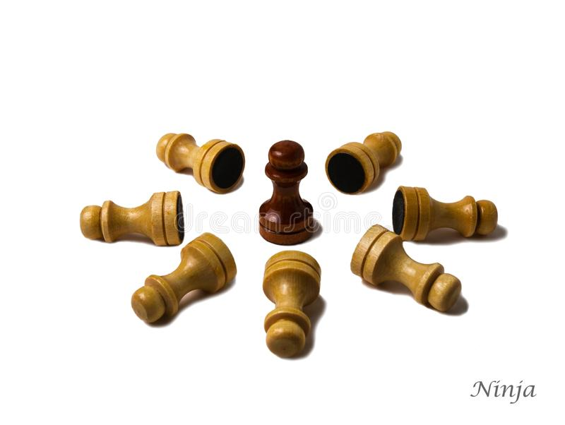 Ninja. A brown chess pawn surrownded by seven laying white-yellowish pawns.  victory over enemies. Isolated against the white background royalty free stock image