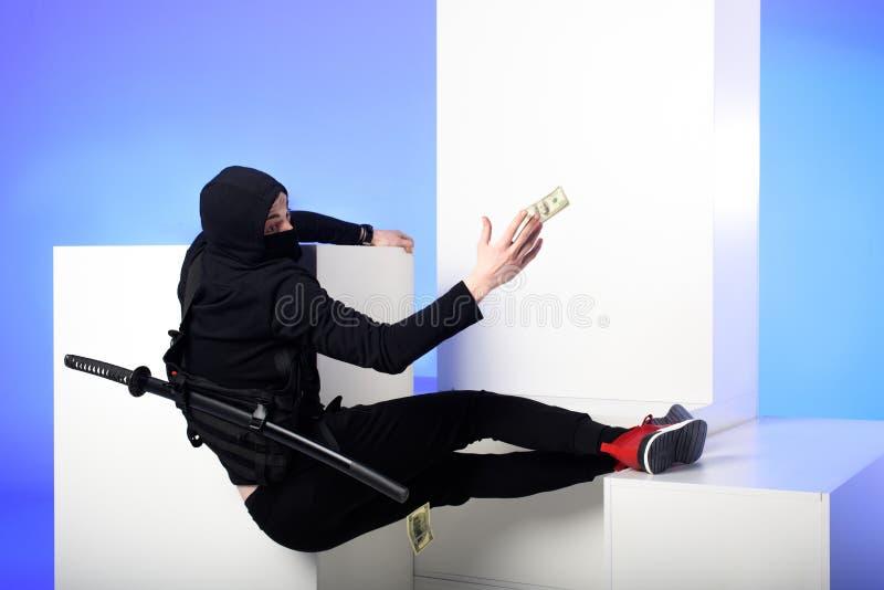 ninja i svarta bekläda fånga dollarsedlar på vita kvarter royaltyfri foto