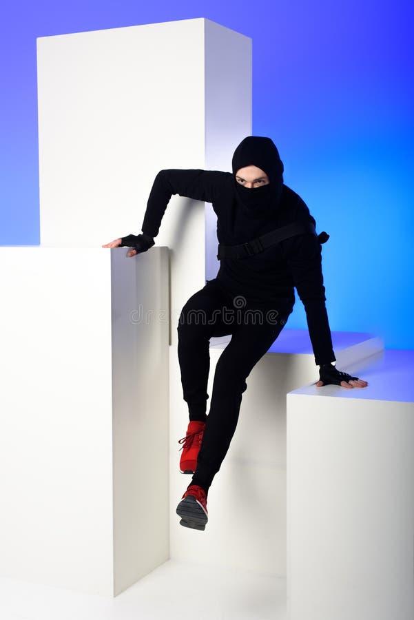 ninja i svarta kläder med katana bak att få över på det vita kvarteret arkivfoton