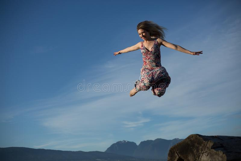 Ninja jak skok kobiety powietrza niebieskiego nieba tło obraz stock