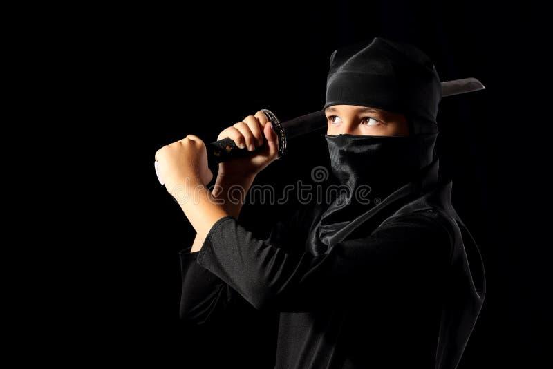 Ninja kid. Little boi playing with katana in ninja costume on dark background stock images