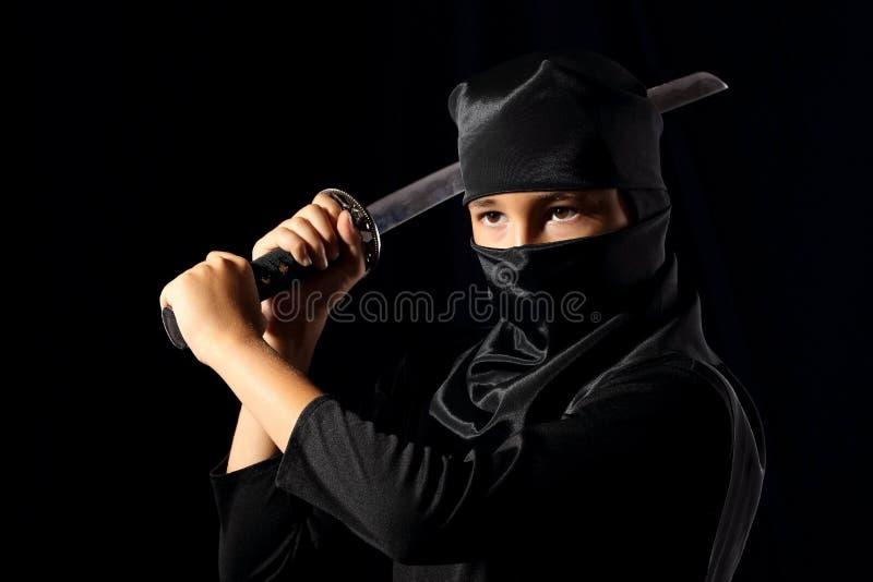 Ninja kid. Little boi playing with katana in ninja costume on dark background stock photo