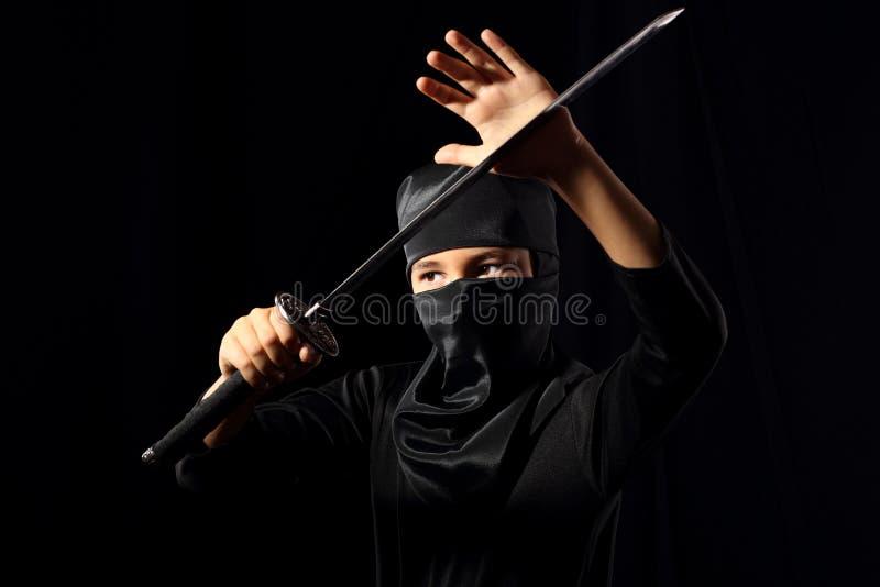 Ninja kid. Little boi playing with katana in ninja costume on dark background stock image