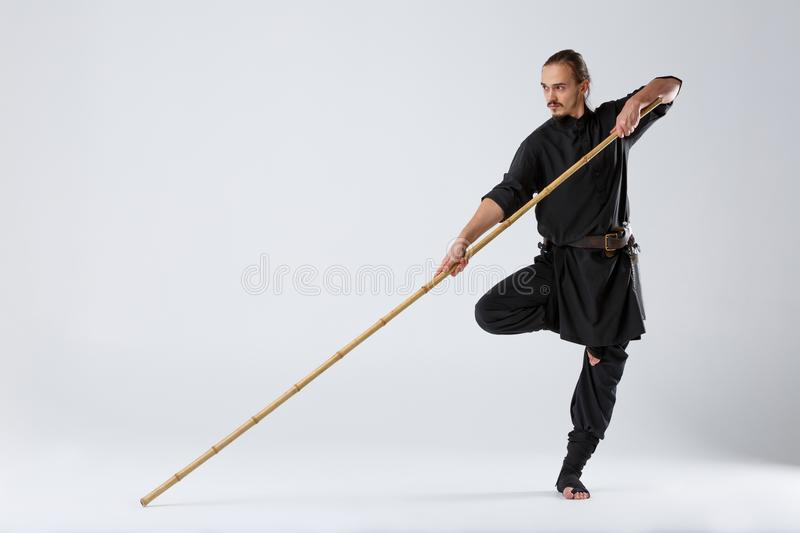 A ninja man in a black kimono, standing in a fighting posture on one leg and holding a fighting stick. royalty free stock photo
