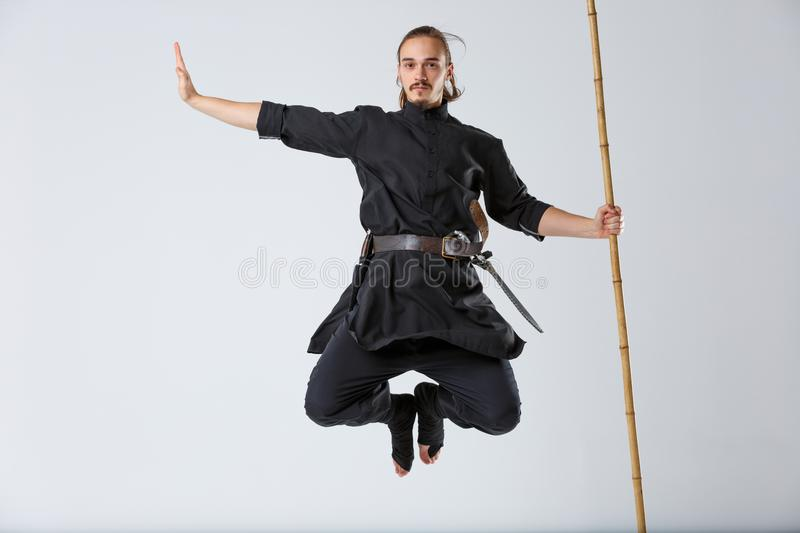 A ninja man in a jump holds a battle stick vertically on a gray background. A ninja man in black uniform with a calm face in a jump holds the combat stick stock photos