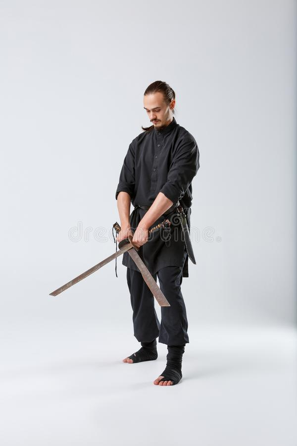 A ninja man, holds two old rusty blades crossed from the blade. stock photos