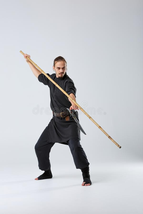 A ninja man is practicing fighting with a bamboo fighting stick. stock image