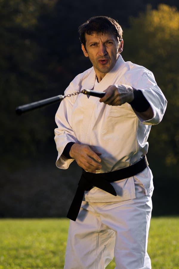 Ninja med nunchaku royaltyfria bilder