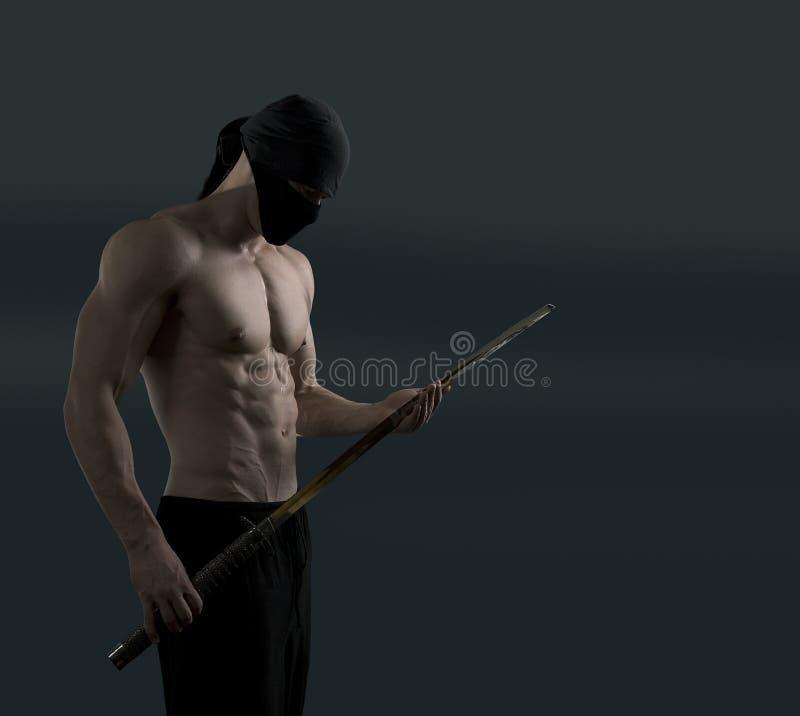 Ninja pull out the katana sword. Athletic ninja with katana sword on a dark background royalty free stock photos