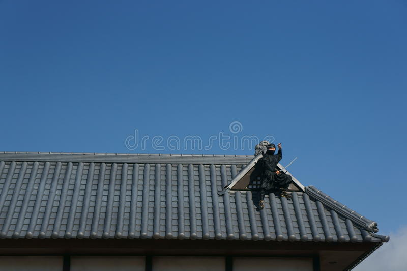 Ninja on the roof. Statue of a ninja on top of a roof holding a sword in broad daylight stock photography