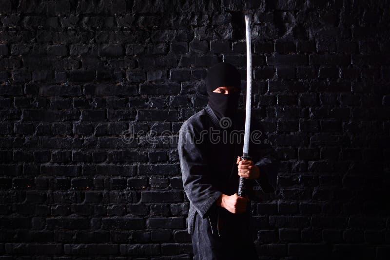 Ninja samurajer med katana i attack poserar på en mörk bakgrund för tegelstenvägg arkivfoto