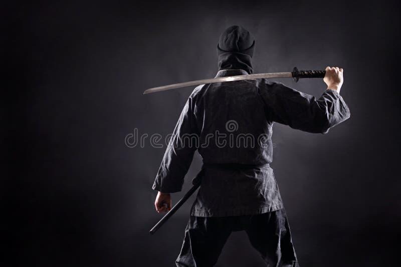 Ninja samurajer med katanaställningar med hans baksida till tittaren arkivfoto