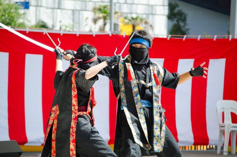 Ninja som är cosplay i stridighetkapacitet med svärdexpertis på etappen på den Matsuri japanfestivalen arkivbild