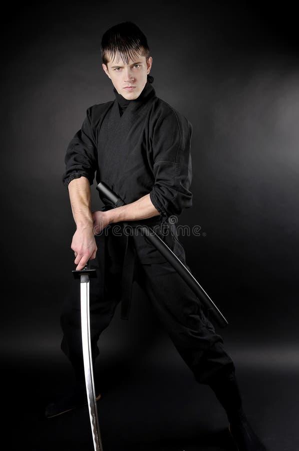 Ninja - spy, saboteur. Stealth assassin of feudal Japan. Ninja with sword over dark background stock images