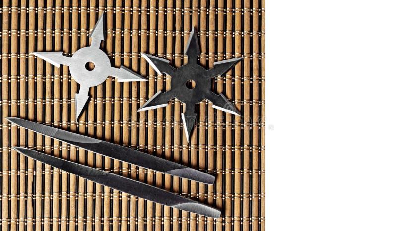 Ninja Star Shurikens med att kasta grova spikar på träbakgrund, royaltyfri bild