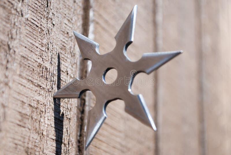 Ninja star. Silver ninja star embedded in wall stock photos