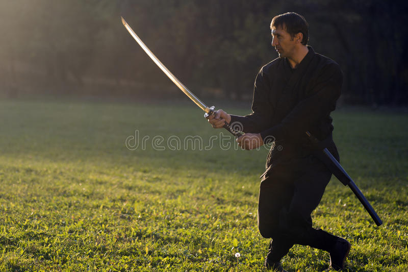 Ninja with sword. Black ninja is practicing martial arts with sword outdoors in nature royalty free stock photo