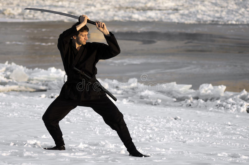 Ninja with sword at winter. Ninja in black kimono with sword is practicing martial arts in the snow at winter stock image