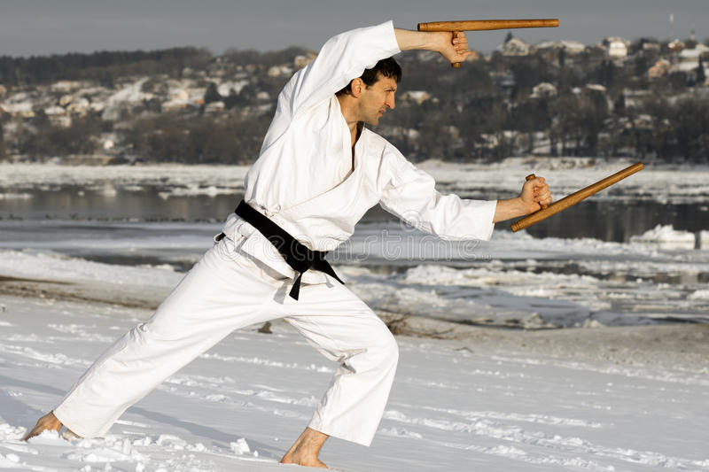 Ninja with tonfa in snow. Ninja in white kimono is practicing with tonfa outdoors at winter barefoot in the snow stock image
