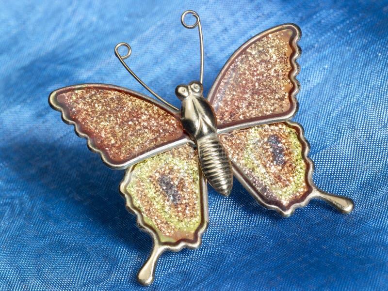 Ninnolo della farfalla sui tessuti blu fotografie stock
